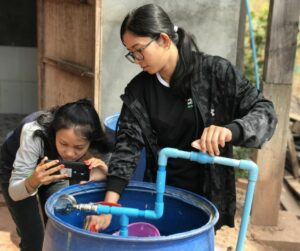 Chanrika (left) and Mariny (right) from the EWB Australia in Cambodia team assess water pressure