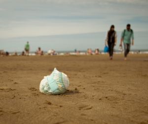 A dispobale nappy discarded on a beach