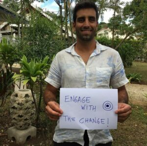 EWB field professional Daniel in Vanuatu holding a sign that says 'Engage with change'